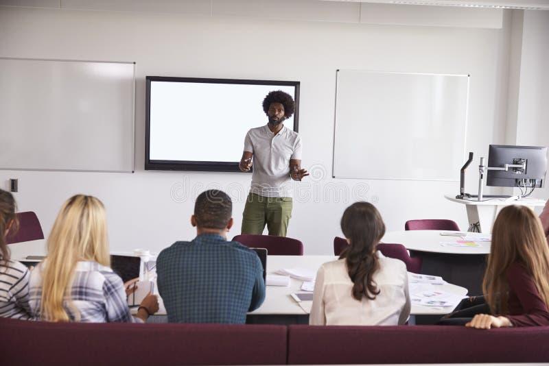 Hochschulstudenten, die auf dem Campus Vortrag besuchen stockbilder