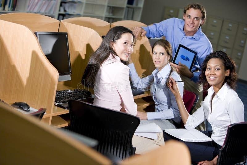Hochschulstudenten, die am Bibliothekscomputer sitzen stockfotografie