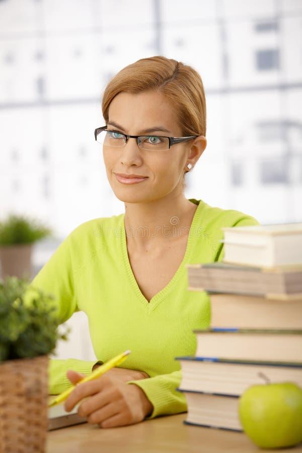 Hochschulstudentmädchen am Schreibtisch stockbilder