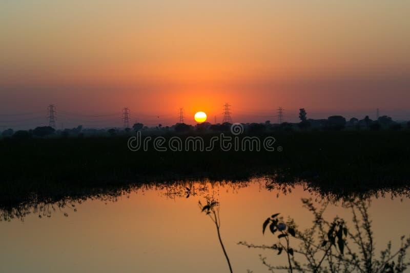 Hochspannungs-Strom-Stromleitungen und Sonnenuntergang stockfotos