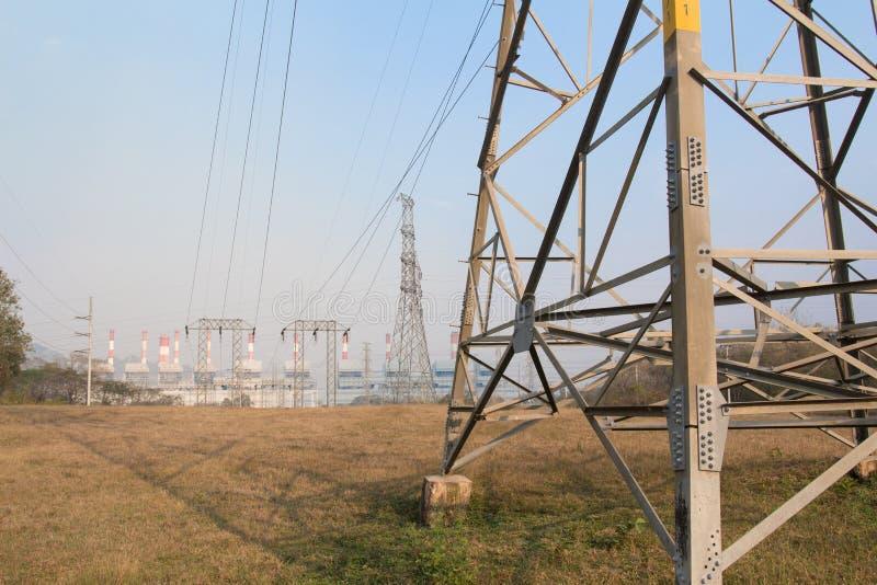 Hochspannungsbeitrag und Kraftwerkhintergrund lizenzfreie stockbilder