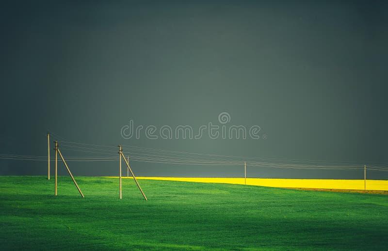 Hochspannungsleitungen und Landschaft Gewitter über einem Feld Stürmischer Himmel und dunkle Wolken lizenzfreie stockfotos