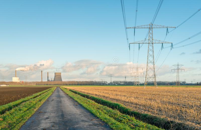 Hochspannungsmasten und Linien in einer ländlichen Landschaft lizenzfreie stockfotografie