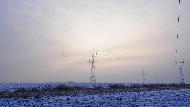 Hochspannungspfosten belichtet durch eine Sonne versteckt im Nebel stockbild