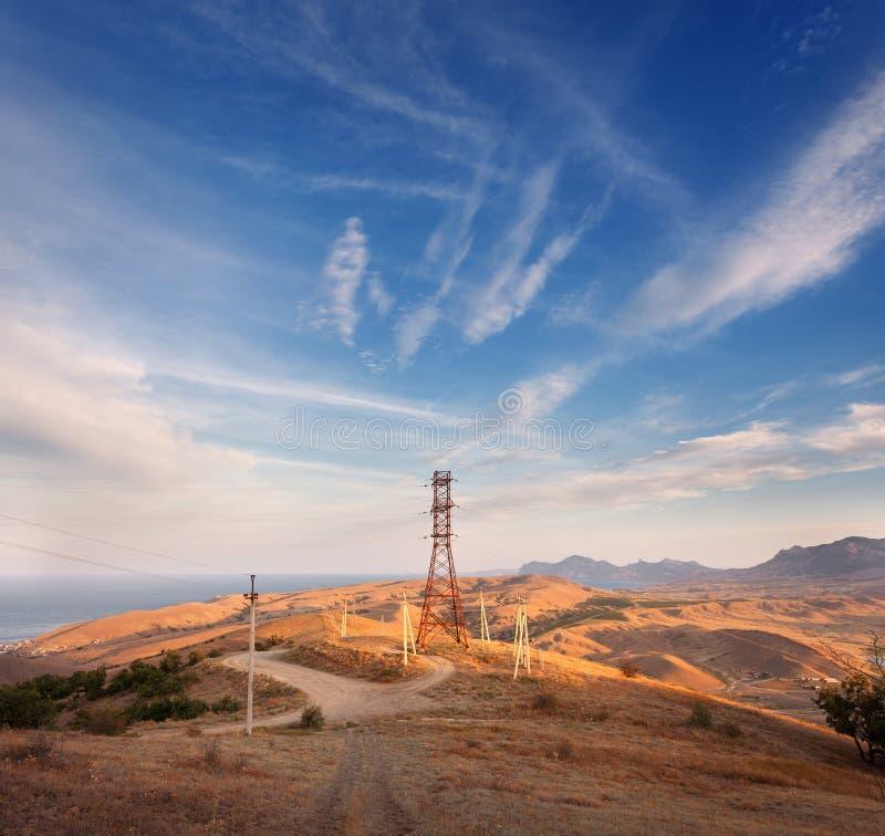 Hochspannungsturm in den Bergen bei Sonnenuntergang Strompylonsystem stockbilder