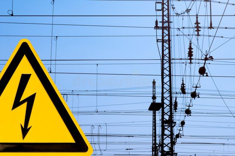 Hochspannungszeichen und obenliegende Bahnverdrahtung stockbilder
