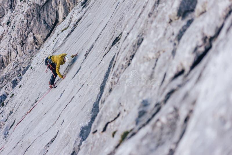 Hochwinkelaufnahme einer Person, die in den Alpen in Österreich auf einen Felsen klettert - Konzept der Herausforderungen überwin lizenzfreie stockfotografie