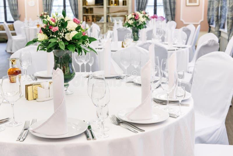 hochzeit bankett Rundtisch für Gäste, gedient mit Tischbesteck, Blumen und Tonware und mit einer Tischdecke bedeckt lizenzfreies stockbild