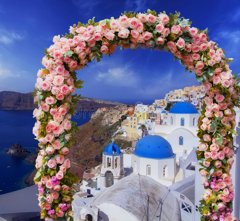 Hochzeit bei Santorini Schöner Bogen höchstens verziert mit Blumen von Rosen mit blauer Kirche von Oia, Santorini, Griechenland r lizenzfreie stockbilder