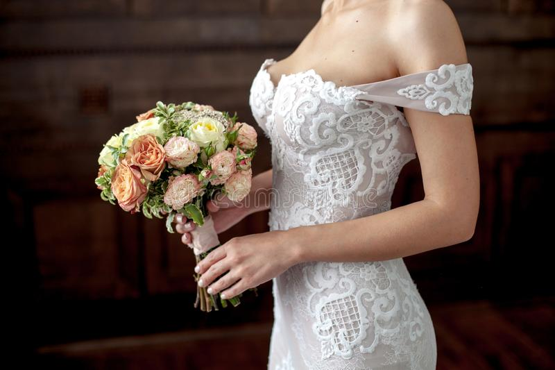 hochzeit Blumenstrauß in der Brauthand Braut im weißen Kleid auf dunklem Hintergrund Kopieren Sie Raum für Text lizenzfreie stockbilder