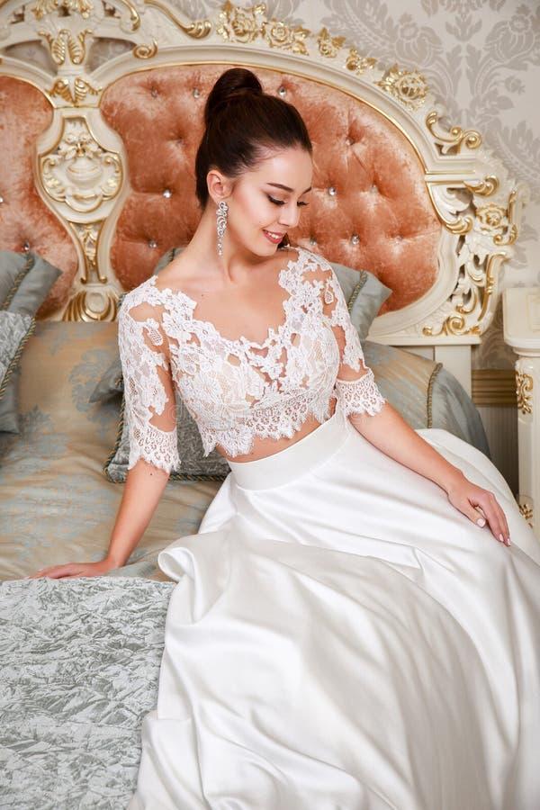 hochzeit Braut im schönen Kleid, das auf Sofa im weißen Studioinnenraum sitzt, mögen zu Hause Modische Hochzeitsart lizenzfreie stockfotografie