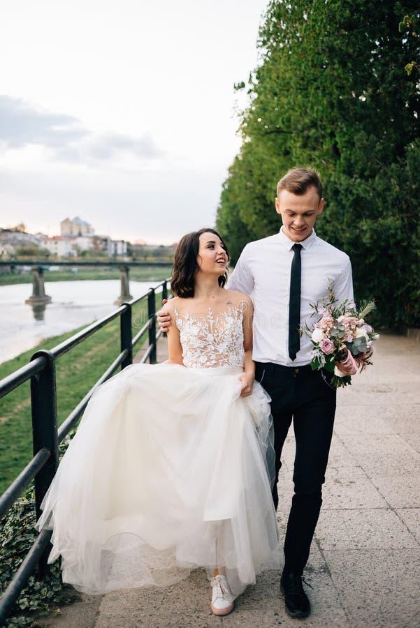 Hochzeit, Braut und Bräutigam gehen die Straße hinunter Weg an Ihrem Hochzeitstag lizenzfreies stockfoto