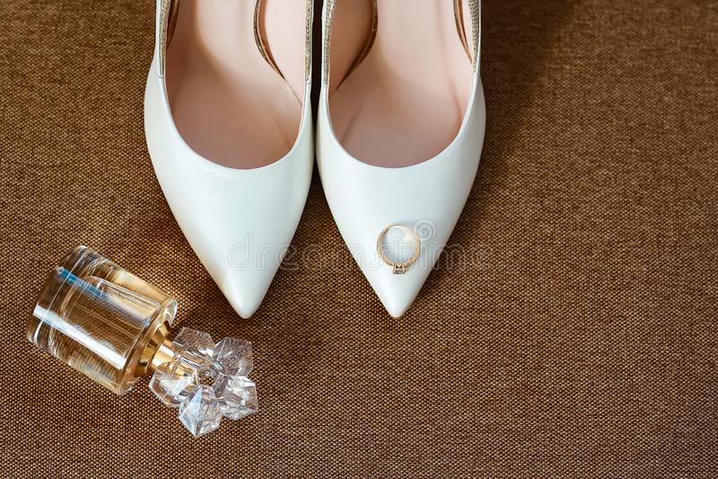 hochzeit dekor Die Schuhe der Braut, Parfüme und schöner Ehering auf einem braunen Hintergrund stockfotos