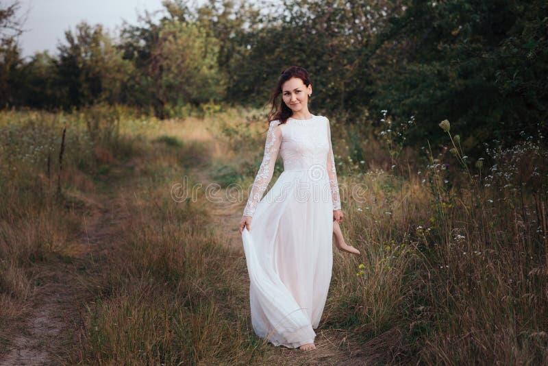 hochzeit Junge schöne Braut mit der Frisur und Make-up, die im weißen Kleid aufwerfen stockfotografie