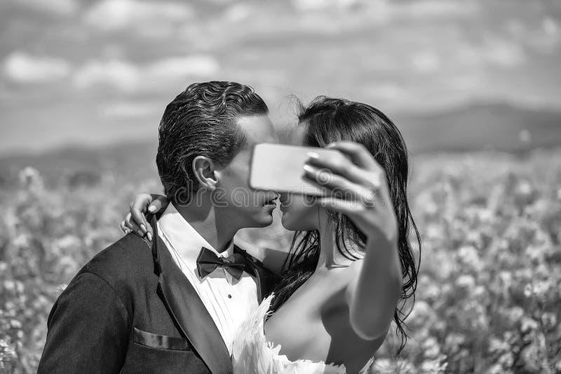 Hochzeit selfie Hochzeitspaarkuß in den Feldgelbblumen lizenzfreie stockbilder
