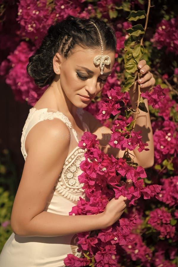 Hochzeit und Feier der Frauen Tages Frauenhaltung mit blühenden Blumen Mode-Modell mit dem Brunettehaar im Garten lizenzfreies stockfoto
