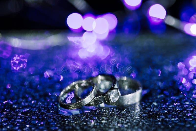 Hochzeit und Verlobungsringe des Weißgolds oder des Silbers auf funkelndem purpurrotem nass Hintergrund mit Wassertropfen Kopiere stockfotografie