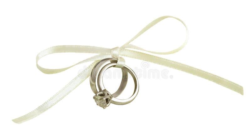 Hochzeit und Verlobungsringe gebunden mit weißem Seidenband stockfotos