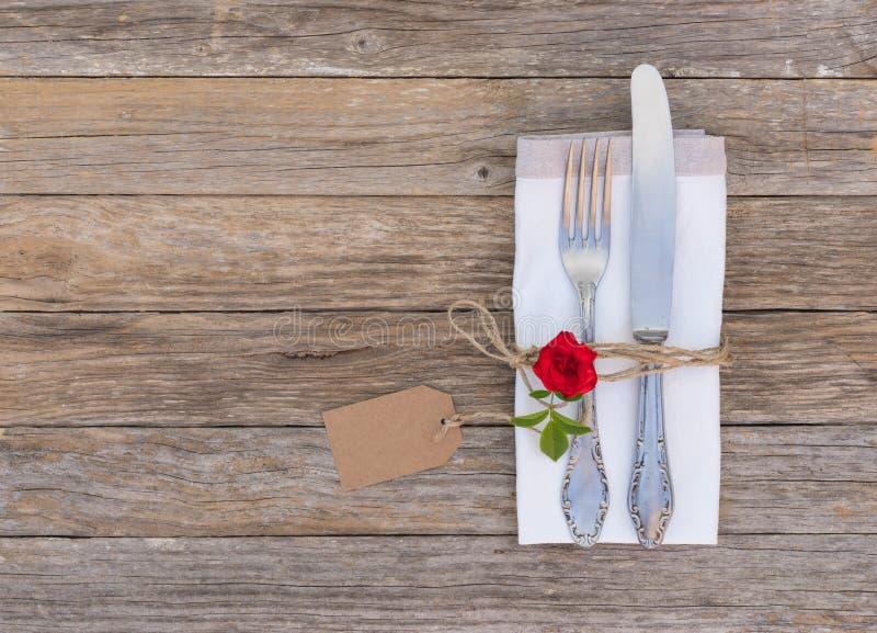 Hochzeits- oder Valentinsgrußabendessenkonzept, Gedeck mit eleganter silberner Tischbesteckrot-Rosenblume und Empty tag lizenzfreies stockbild