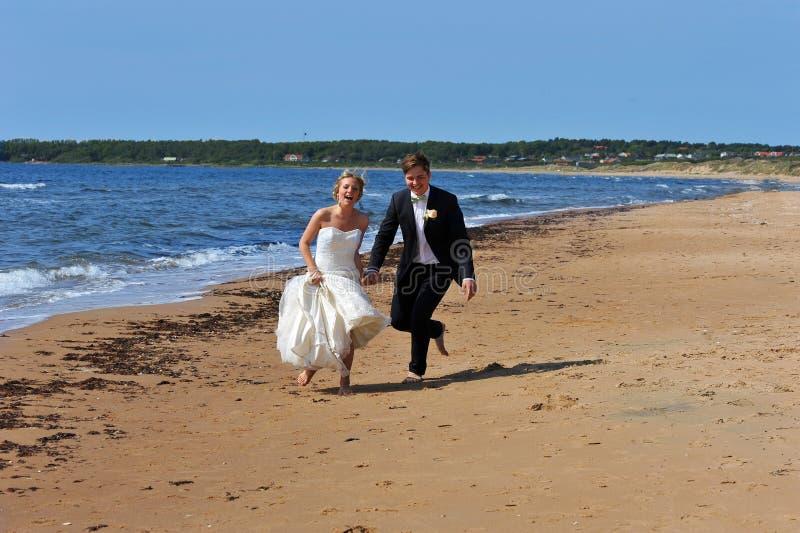 Hochzeits-Paare auf dem Strand-Lachen. stockfotos