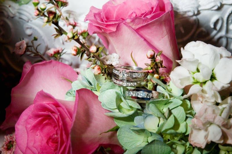 Hochzeits-Ringe im Blumenstrauß stockbilder