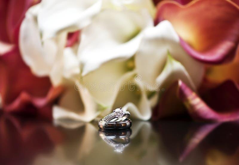 Hochzeits-Ringe und Blumen stockfotografie