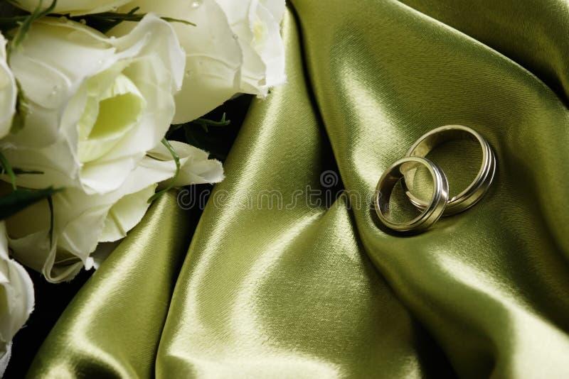 Hochzeitsbänder auf grünem Satin lizenzfreie stockfotos