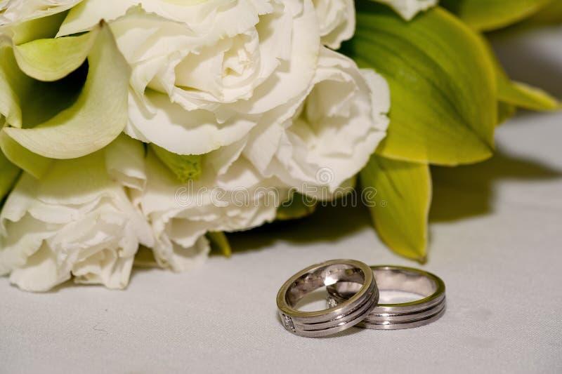 Hochzeitsbänder mit weißen Rosen stockfotos