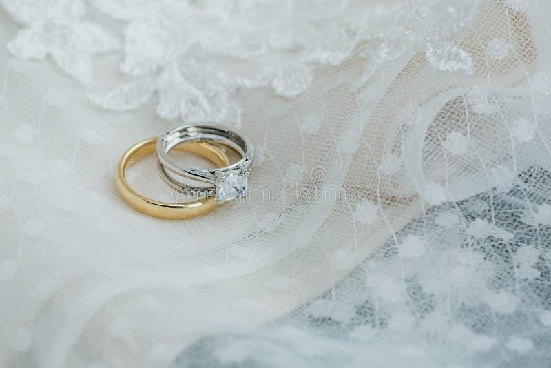Hochzeitsbänder schließen oben auf Hochzeitskleidergewebe stockbild