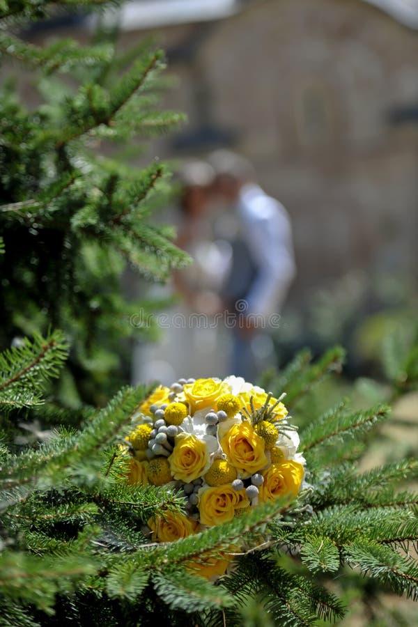 Hochzeitsblumen stellten auf immergrünen Baum mit unscharfer Braut und gro ein lizenzfreie stockfotos