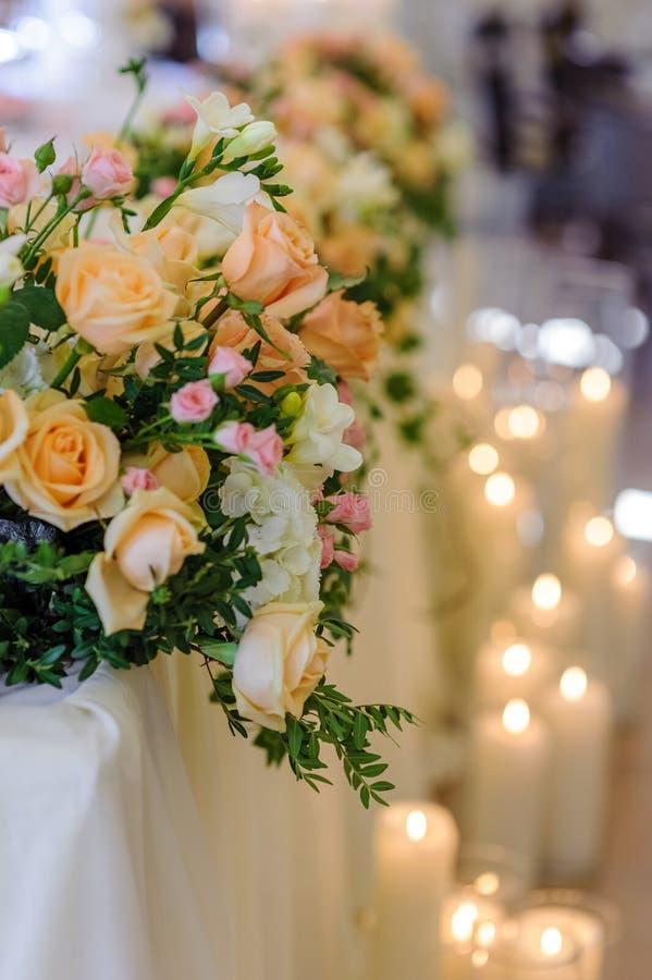 Hochzeitsblumenanordnung auf dem Hintergrund von brennenden Kerzen stockfoto