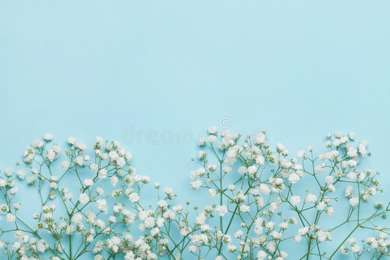 Hochzeitsblumenrahmen auf blauer Tabelle von oben flache Lageart stockfotos
