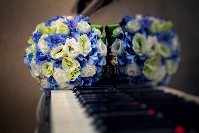 Hochzeitsblumenstrauß auf dem Klavier stockbild