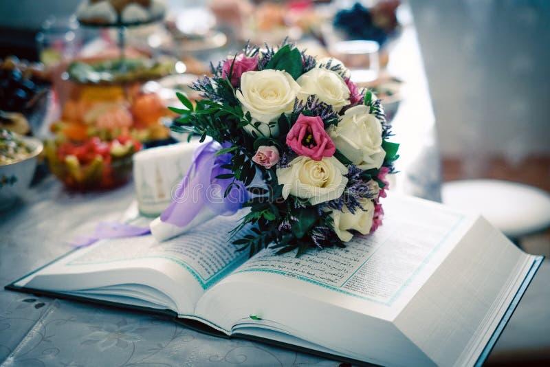 Hochzeitsblumenstrauß auf dem Koran lizenzfreie stockfotografie