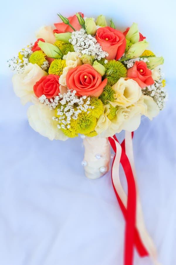 Hochzeitsblumenstrauß auf dem weißen Hochzeitskleid lizenzfreies stockbild