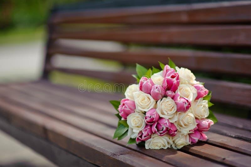 Hochzeitsblumenstrauß auf hölzerner Bank lizenzfreies stockfoto