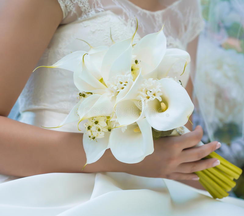 Hochzeitsblumenstrauß in den Händen der Braut lizenzfreies stockbild