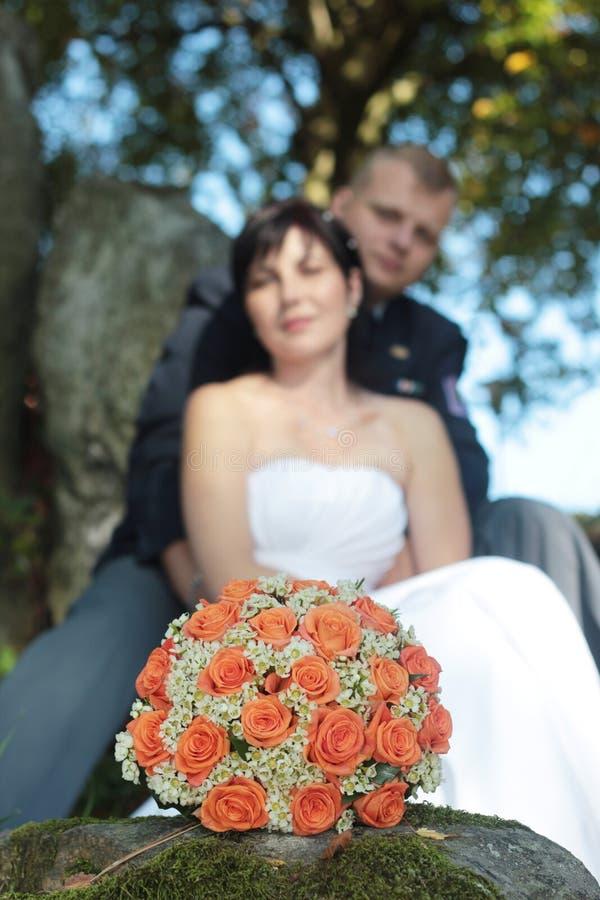 Hochzeitsblumenstrauß eben und verheiratetes Paar lizenzfreie stockbilder