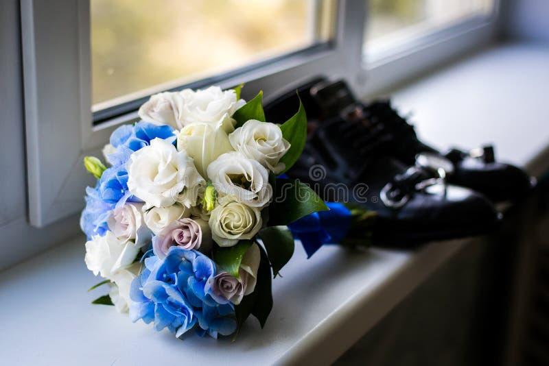 Hochzeitsblumenstrauß am Fenster die Attribute des Bräutigams Eben verheiratetes Paar die Vorbereitungen des Bräutigams stockfotografie
