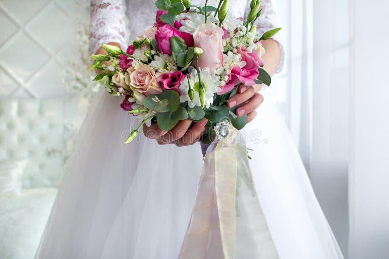 Hochzeitsblumenstrauß im bride& x27; s-Hände lizenzfreie stockfotos