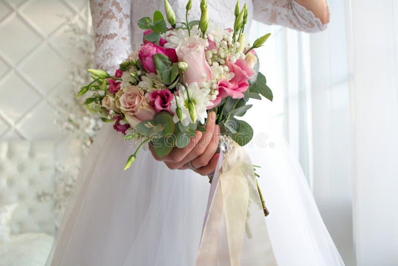 Hochzeitsblumenstrauß im bride& x27; s-Hände stockbild