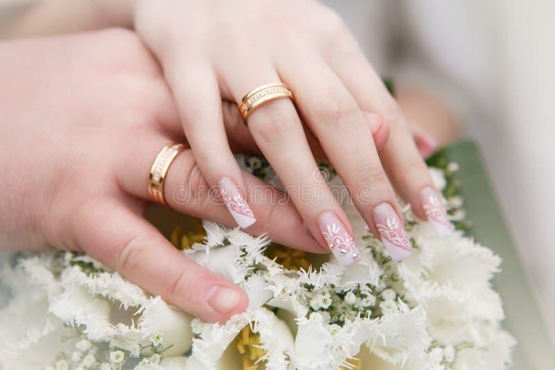Hochzeitsblumenstrauß mit den Händen und den Ringen lizenzfreies stockfoto