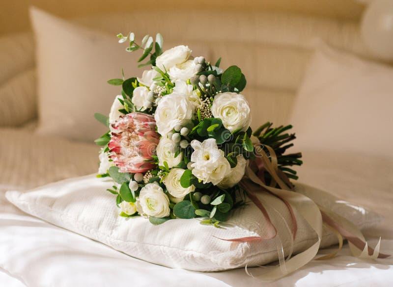 Hochzeitsblumenstrauß mit zarten Blumen auf Bett lizenzfreie stockfotos