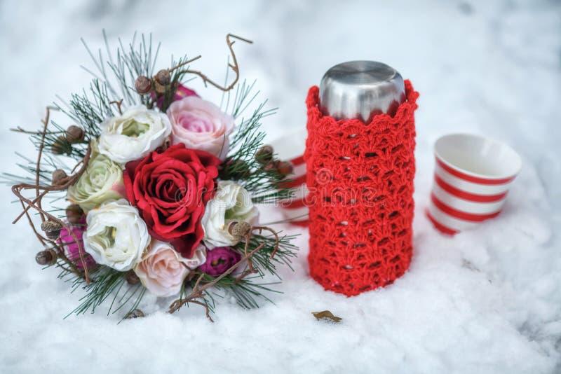 Hochzeitsblumenstrauß, -Thermosflasche und -becher im Schnee lizenzfreie stockbilder
