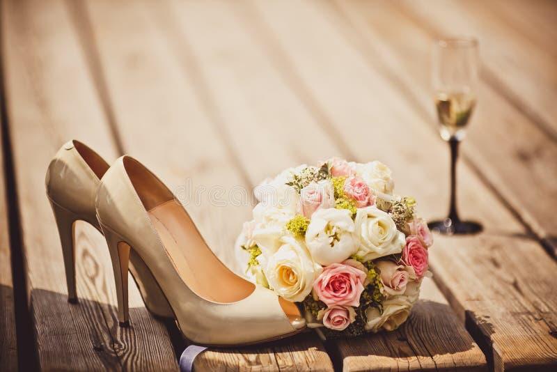 Hochzeitsblumenstrauß- und -brautschuhe stockfotos