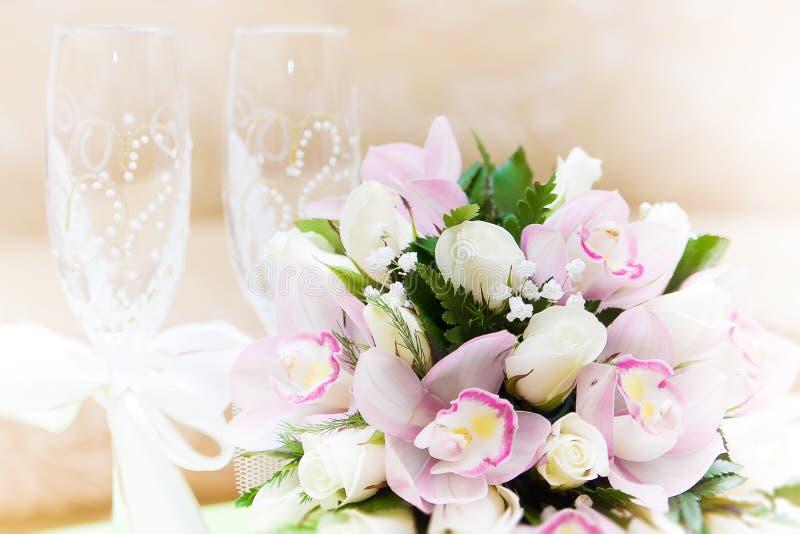 Hochzeitsblumenstrauß- und -weingläser im Hintergrund stockbilder