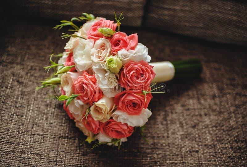 Hochzeitsblumenstrauß von den roten und weißen Rosen, die auf brauner Beschaffenheit liegen lizenzfreies stockfoto
