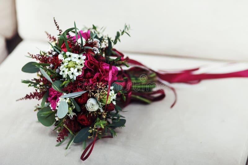 Hochzeitsblumenstrauß von Rosen, von Ranunculus und von Pfingstrose liegt auf einem weißen c stockbilder