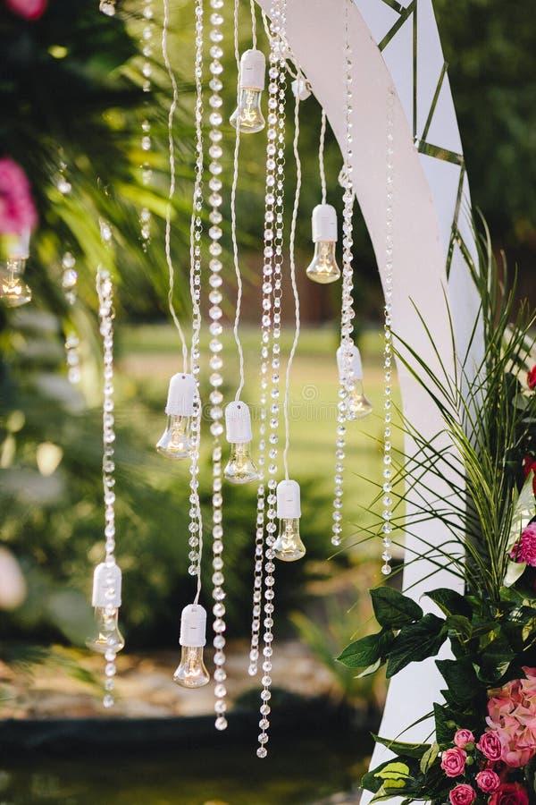 Hochzeitsbogen-Dekorationsnahaufnahme Anhänger gemacht von den Kristallen und von den Glühlampen Nahaufnahme, Blumen und Palmblät lizenzfreie stockfotografie