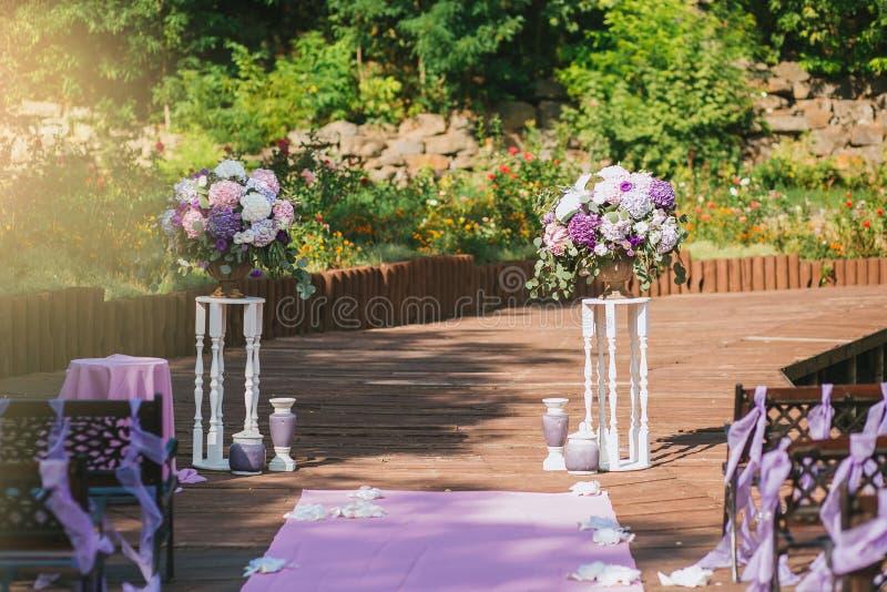 Hochzeitsbogen in einem Sommergarten auf einer Terrasse von weißen Sockeln der Weinlese mit purpurroten Blumensträußen der Blumen lizenzfreies stockbild